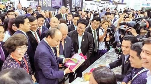 hủ tướng Nguyễn Xuân Phúc tham quan gian hàng trưng bày gạo mang thương hiệu Cỏ May tại Hội chợ ThaiFex tổ chức tại Thái Lan